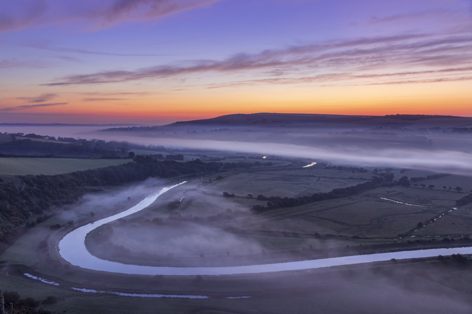 A new day dawns over the Cuckmere valley from High and over south downs east Sussex south east England